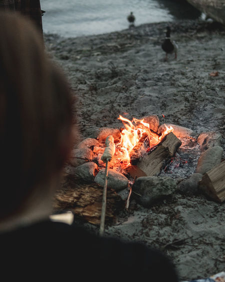Campfire with friends Burning Heat - Temperature Fire Flame Fire - Natural Phenomenon Bonfire Nature Real People One Person Leisure Activity Glowing Land Camping Beach Selective Focus Campfire Log Women Rear View Outdoors Wood