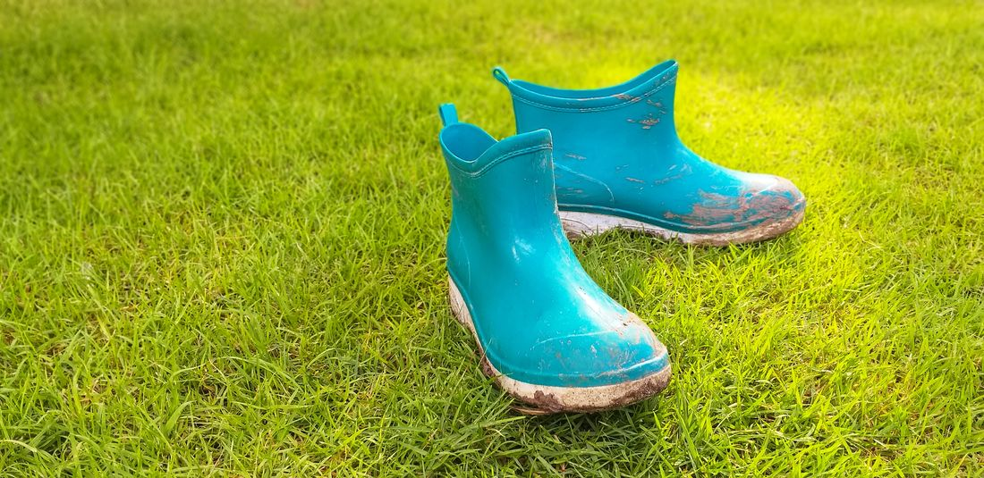 The view of the mud boots. Absence Blue Boot Close-up Compatibility Day Field Grass Green Color Growth High Angle View Land Nature No People Outdoor Play Equipment Outdoors Pair Plant Playground Rubber Boot Shoe