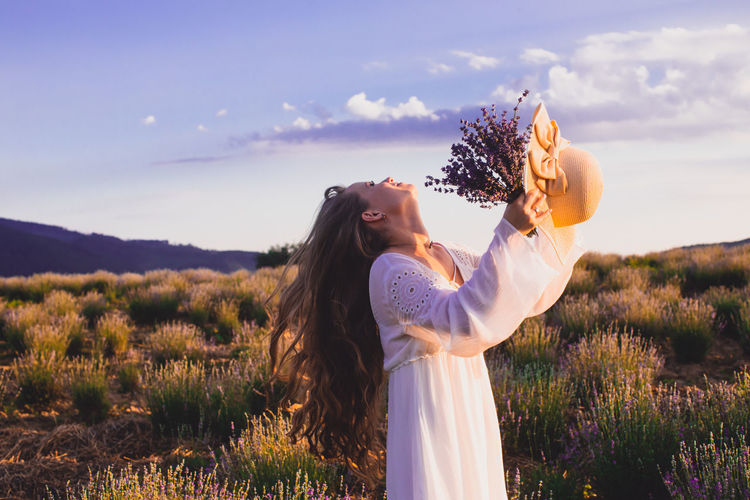 Woman standing by flowers on field against sky