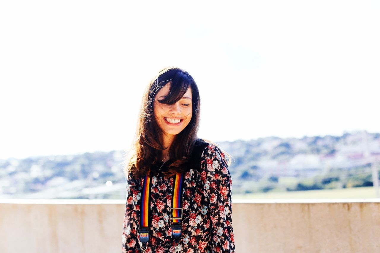 Smiling young woman standing at rooftop against clear sky