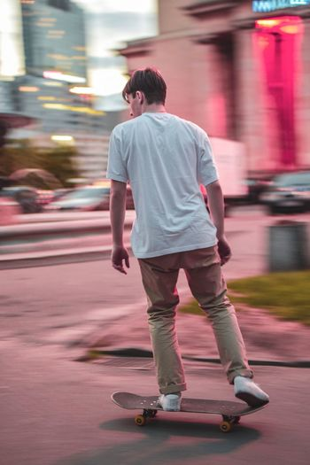 Movement Panning Full Length One Person Skateboard Motion City Rear View Casual Clothing Men on the move Leisure Activity Shorts Street Young Men City Life