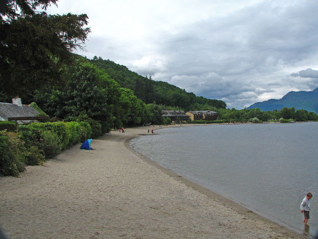 The beach in the pretty village of Luss, near Glasgow, Scotland Luss, Scotland Mountain Range Background Beauty In Nature Boy On Beach Day Mountain Nature No People Outdoors Sandy Beach Scenics Sky Tranquil Scene Tranquility Tree Water Beach On The Clyde Paddling