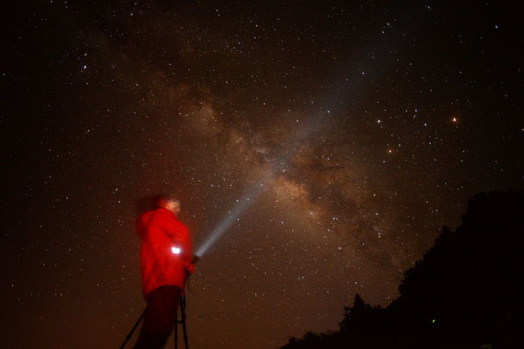 Low Angle View Of Person With Flashlight Against Star Field At Night