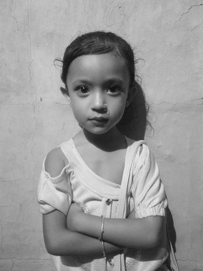 Portrait of girl with arms crossed standing against wall