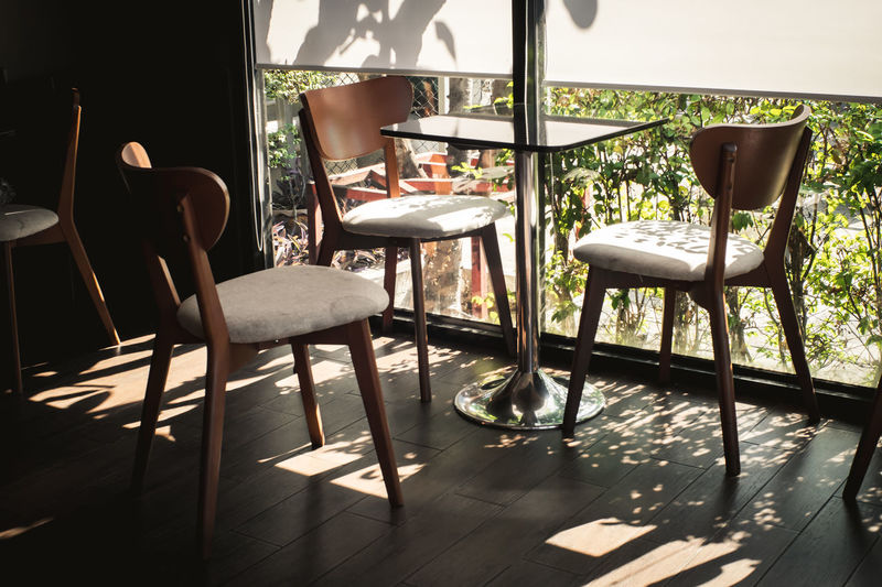 Vintage Chairs and Table near glass window in the coffee shop, Sunlight coming through the window, with Shadow on the wooden floor, with beautiful small garden outside the room. Focus at the table. Calm Light Living Modern Relaxing Room Sunlight Travel Absence Cafe Chair Day Decoration Floor Furniture Home Interior Home Showcase Interior Indoors  Lifestyles Light And Shadow No People Seat Space Sunlight Table