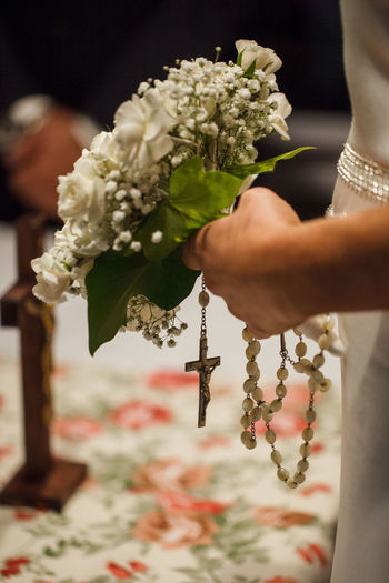 Midsection Of Bridegroom Holding Bouquet And Rosary Beads During Wedding
