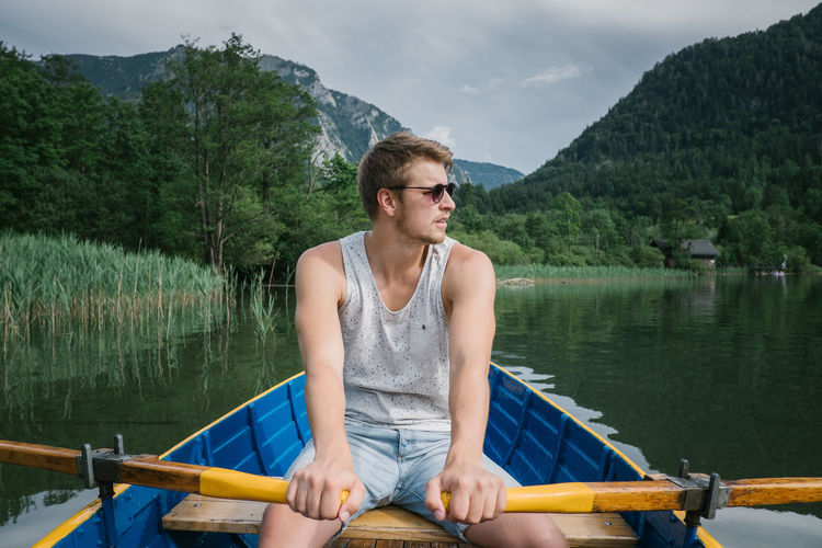 Young man on boat sailing in lake against cloudy sky
