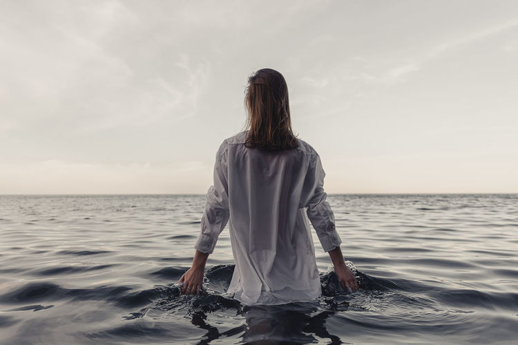 Rear view of woman standing in sea against sky