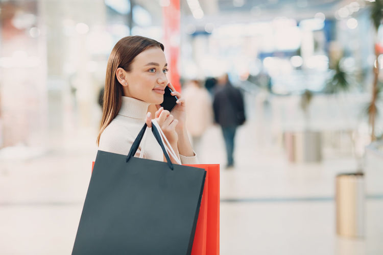 Young woman talking on phone while holding shopping bag outdoors