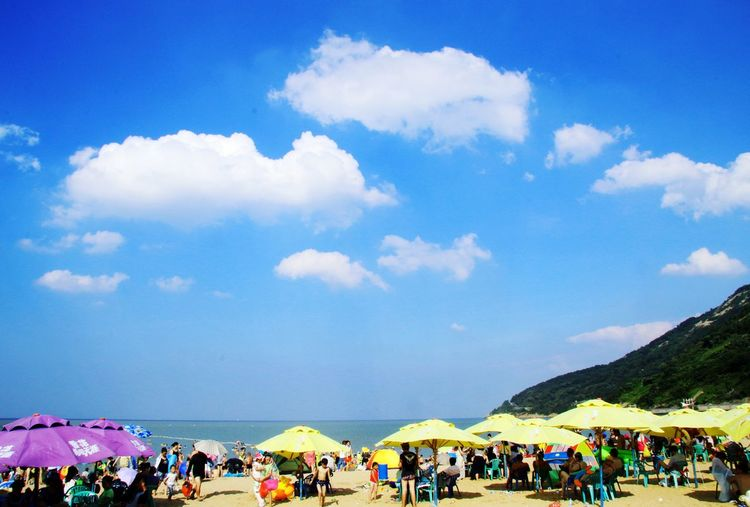 People at beach against blue sky