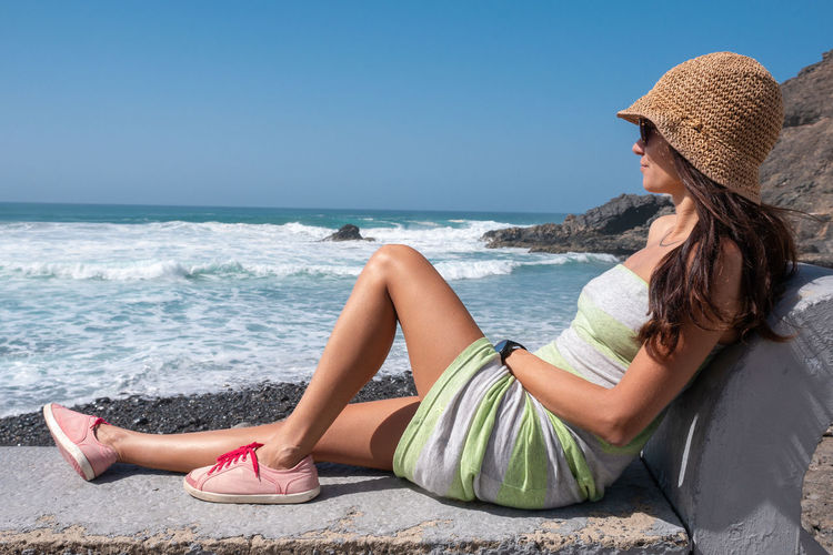 Sea Hat Beach Land Water Leisure Activity Clothing Sitting One Person Full Length Adult Women Relaxation Young Adult Lifestyles Trip Casual Clothing Vacations Side View Holiday Sun Hat Horizon Over Water Outdoors Beautiful Woman Hairstyle