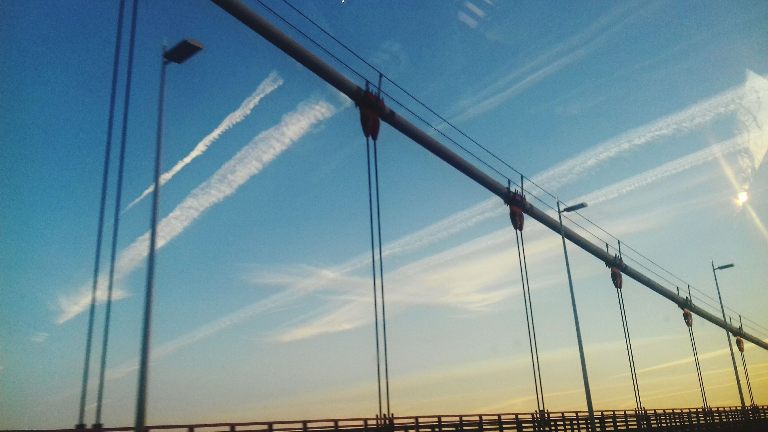 low angle view, sky, blue, connection, transportation, suspension bridge, sunlight, outdoors, built structure, day, bridge - man made structure, engineering, part of, clear sky, steel cable, no people, nature, cable-stayed bridge, metal, cloud - sky