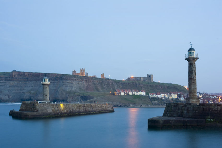 Two breakwater navigation beacons on the ends of the piers on either side of the entrance to Whitby harbour at dusk with St Marys Church and Whitby Abbey visible on Tate Hill in the distance Beacon Breakwater Coastal Copy Space Dusk England Entrance Evening Guidance Guide Harbor Light Lighthouse Lighthouse Navigation North Yorkshire Piers Portrait Sea Tate Hill Tower Town Water Whitby Whitby Abbey