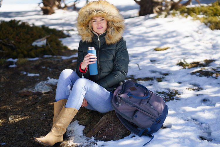 Portrait of woman sitting on snow covered land