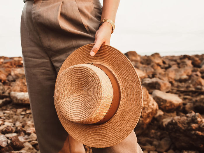 Midsection of woman holding hat