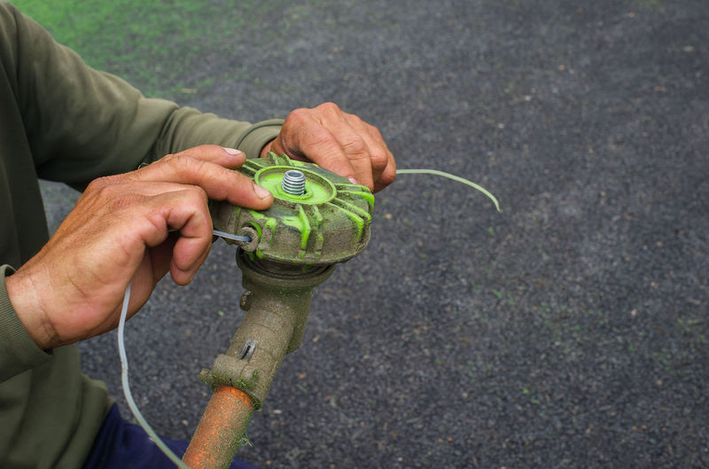 Focus on the hands of technicians who are repairing the head of the mower. Casual Clothing Close-up Cropped Day Focus On Foreground Holding Leisure Activity Lifestyles Nature Outdoors Part Of Selective Focus