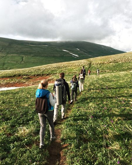 Rear view of boys walking on grassy field against cloudy sky