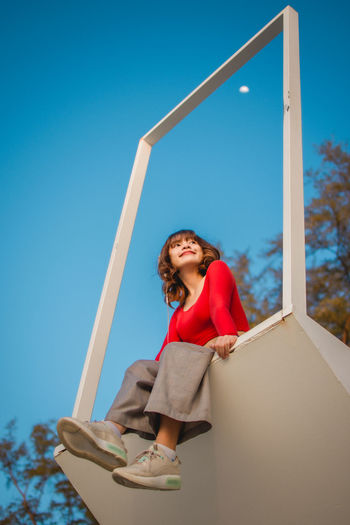 Portrait of smiling young woman standing against blue sky
