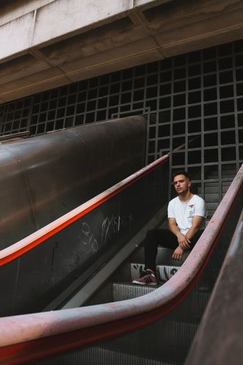 Man sitting on escalator in city