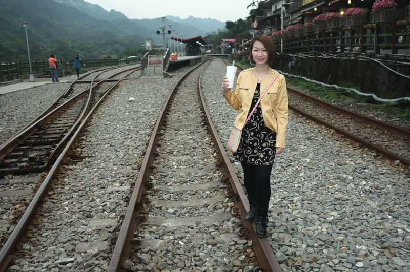 Full length portrait of woman holding disposable cup while standing on railroad track