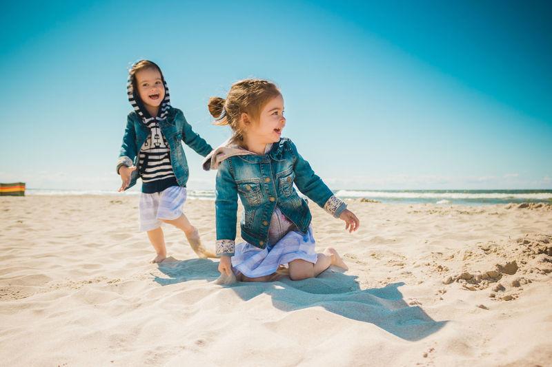 Full length of siblings playing at beach