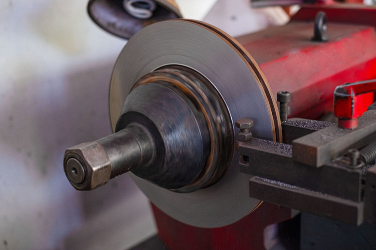 Mechanic man repairing brake use lathe tool polishing disc brakes of cars working automatic