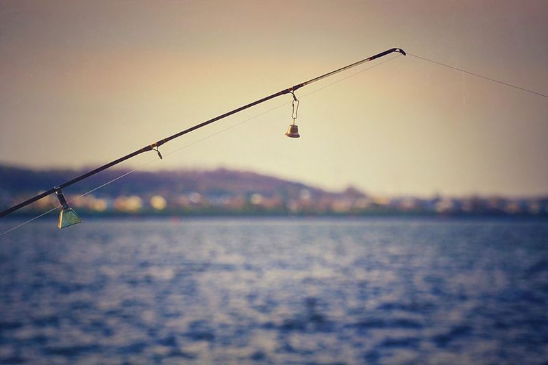 Fishing rod over river against sky