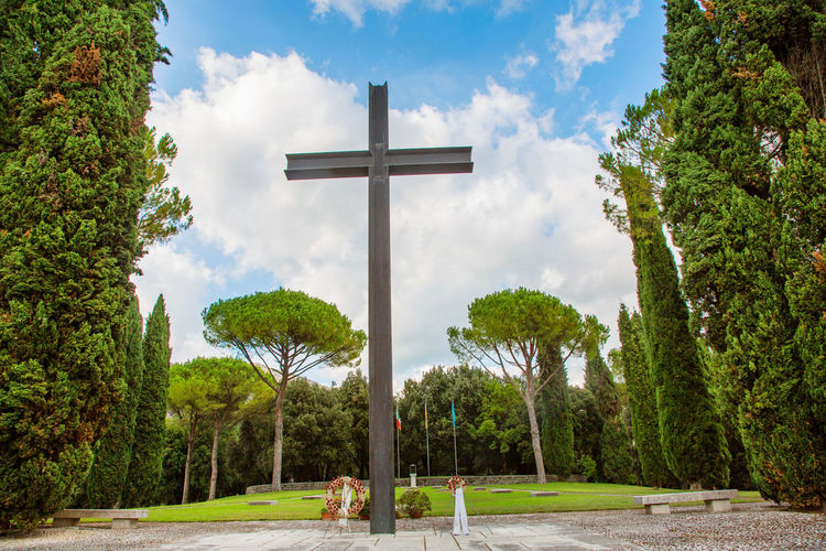 Trees and cross against sky