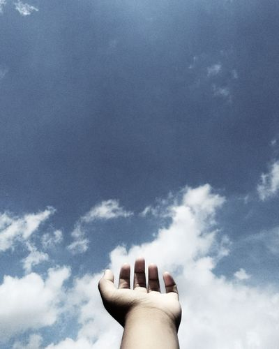 Low angle view of cropped hand against sky