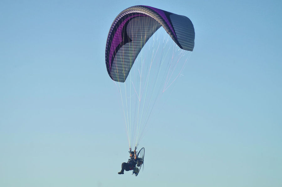 paragliding in the sky Adventure Clear Sky Day Exhilaration Extreme Sports Flying Leisure Activity Lifestyles Low Angle View Men Mid-air Nature One Person Outdoors Parachute Paragliding People Real People Sky Sport Stunt Person Transportation