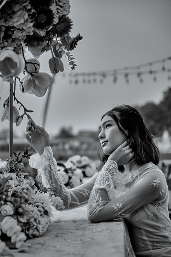 Young woman with flower petals on land against sky