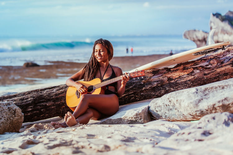 Woman Playing Guitar While Sitting At Beach Against Sky