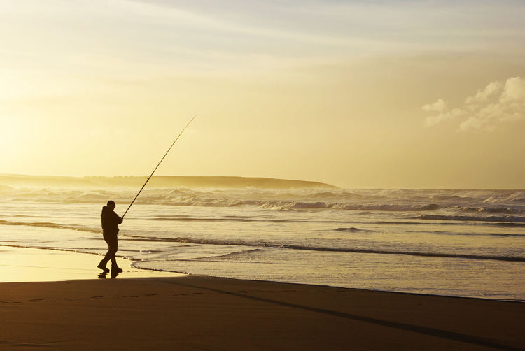 Rear View Of Man Fishing On Beach