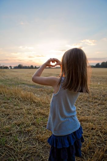 Rear View Of Girl Making Heart Shape With Hands While Standing On Field Against Sky