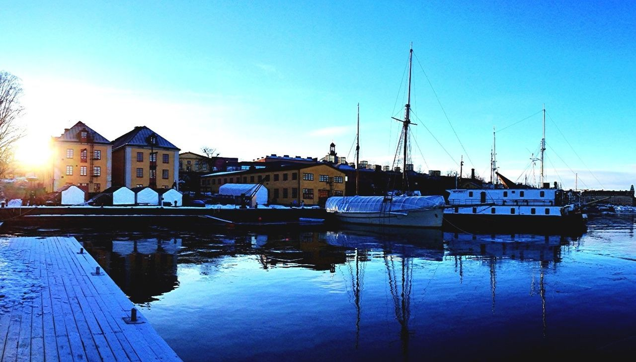 Sailboats Moored In River In Front Of Houses Against Blue Sky During Winter
