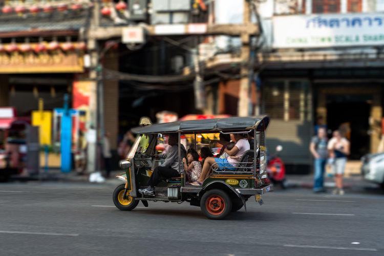 People travelling in jinrikisha on street against buildings