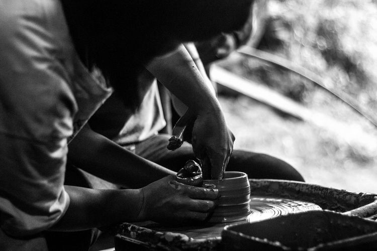 Midsection Of Men Making Earthenware On Pottery Wheel