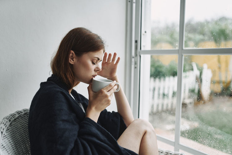 Young woman drinking coffee from glass window