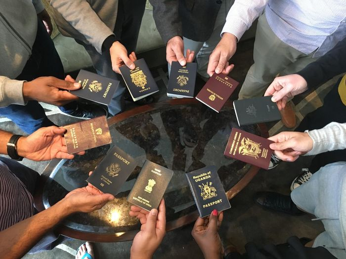 High angle view of people holding passports over table