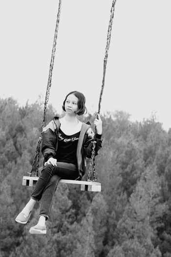 Woman sitting on swing at playground