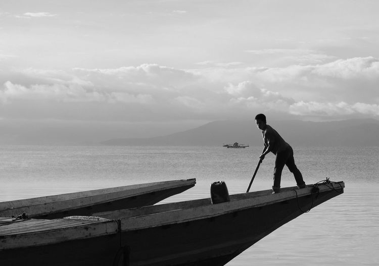 A fisherman parking his traditional boat in the lake of Towuti in the regency of Luwu Timur, South Sulawesi - Indonesia. Fishing Village Harbor Harbour Morning Black And White Blackandwhite Boat Boats Dock Docking Fisherman Fishermen Fishing Fishing Boat Harbor View Men Mode Of Transportation Nautical Vessel Parking Real People Sea Ship Shipping  Transportation Water