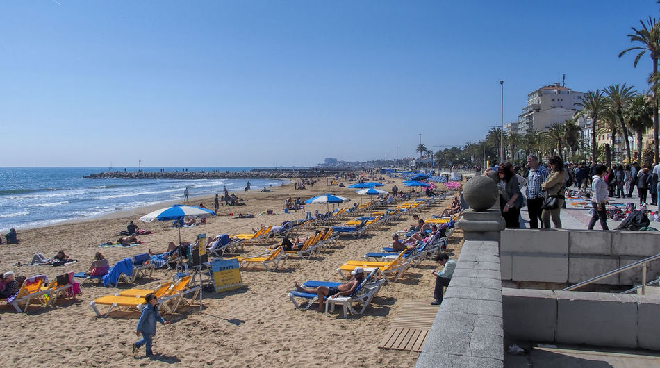 Beach Blue Clear Sky Day Group Of People Horizon Over Water Large Group Of People Leisure Activity Mixed Age Range Nature Outdoors Parasol Relaxation Sand Sea Shore Sitges Barcelona España Sunlight Tourism Vacations Water