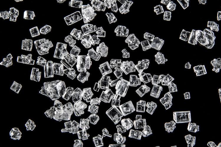 Macro shot of scattered sugar against black background