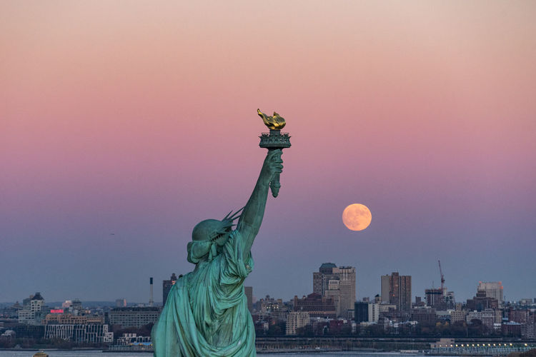 Statue of liberty in city during sunset