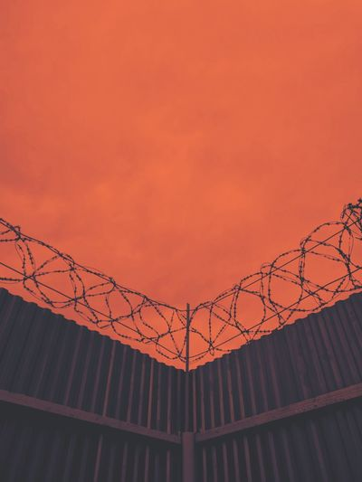 Low angle view of barbed wire on fence against orange sky