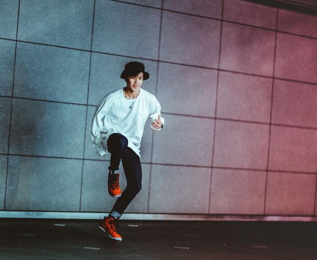 Full length of man running on mobile phone in city
