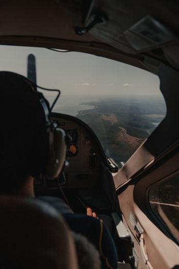 Rear view of man seen through airplane window