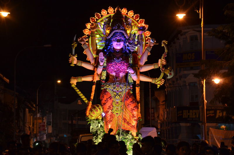 Low angle view of goddess statue on street at night