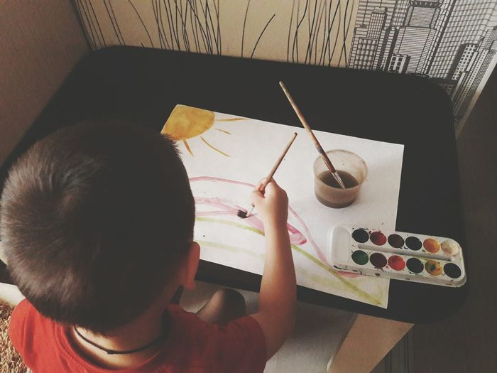 High angle view of boy painting on paper at table