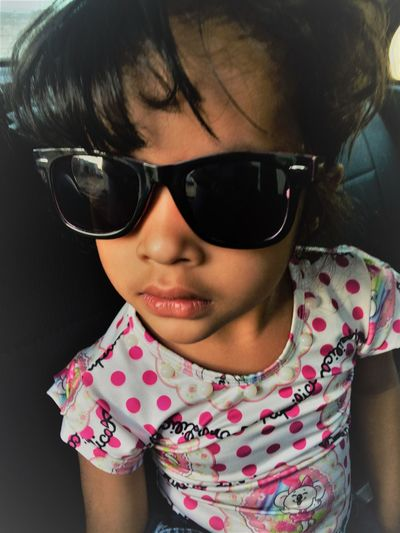 Close-up of girl wearing sunglasses while sitting in car